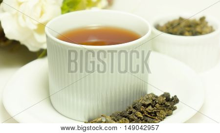Dry oolong tea leaf from China and tea in traditional cup