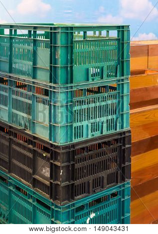 Pastic crate stack near the billboard in the fruit market.