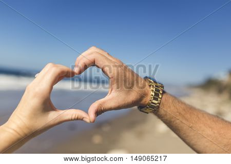 A man and a woman make the shape of a heart with their hands while celebrating their anniversary.