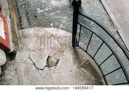 Art street photography. Old stone porch and stairs. Top view on damaged street staircase out of house, made in medieval european style from decorative rock.
