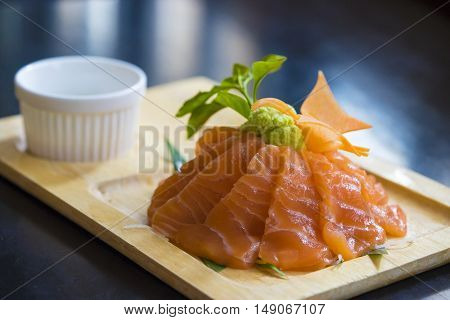 Salmon raw sashimi slice on wooden plate
