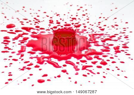Impact of red color water drop on a white surface. Other red drops are in the vicinity of the impact.
