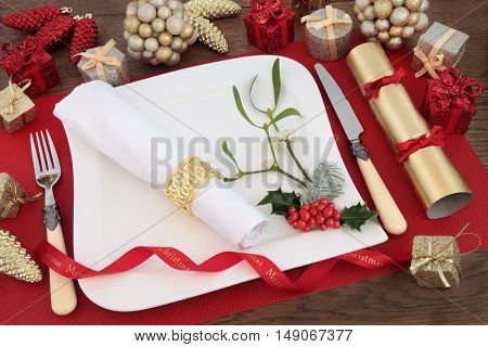 Christmas dinner table setting with white plate, cutlery, linen serviette, holly, mistletoe, bauble decorations and cracker over on a red place mat on oak background.
