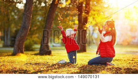 happy family mother and child girl playing and throw leaves in autumn park outdoors