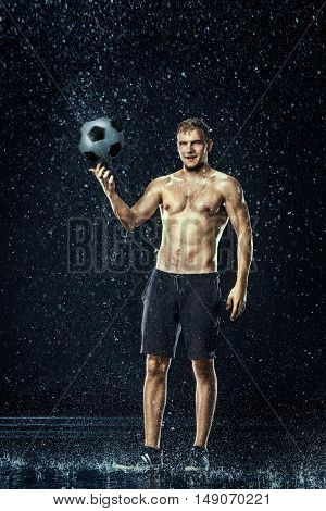 Water drops around football player under water on black background