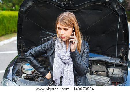 Picture of a helpless young woman with her car broken