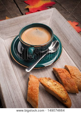 Delicious cup of espresso with cantuccini on a wooden plate