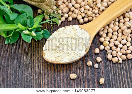 Flour chickpeas in spoonful, chick-peas in a sack and fresh pea pods on a background of wooden boards