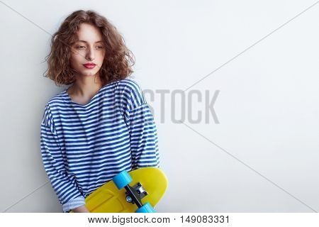 Stylish fashion portrait of trendy casual young woman in striped clothes, posing near white wall with yellow skateboard.