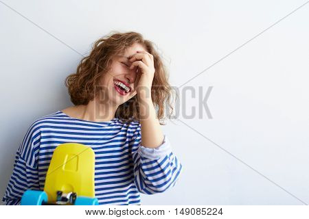 Close up portrait of young beautiful girl having fun and hiding her face with hand while holding a yellow skateboard. Natural makeup and curly hairdo. White background, not isolated. Inside.