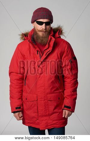 Portrait of a bearded man wearing red winter Alaska jacket and sunglasses, looking at camera, studio shot