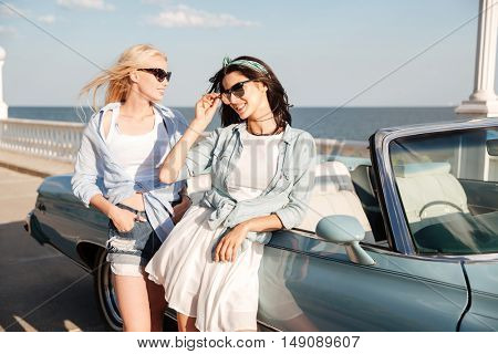 Two beautiful young women standing near cabriolet on promenade