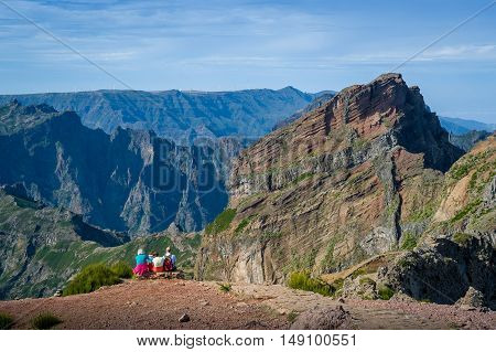 Group of tourists is sitting on the cliff. Pico Arieiro to Pico Ruivo hiking route. Madeira island, Portugal.