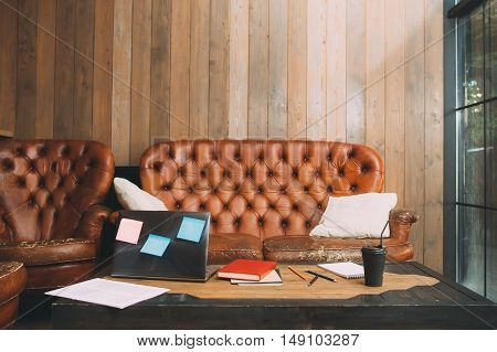 Office working place of unsuccessful worker. Wooden desk with laptop, stationery, old leather sofa and armchairs. Poverty, unemployment, poor business and bankruptcy concept