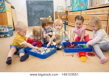 Children improving motor skills of hands with rice and beans
