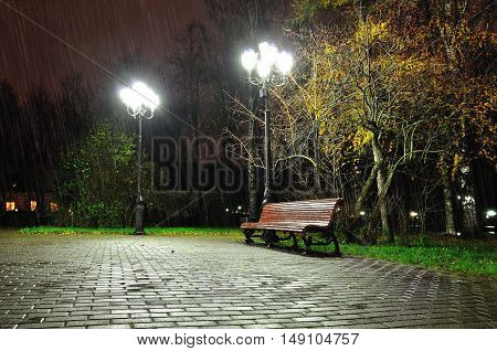 Autumn night landscape of night autumn park. Autumn rainy night with lonely bench under yellowed autumn trees-night autumn landscape. Autumn. Night in autumn city park. Colorful autumn night landscape