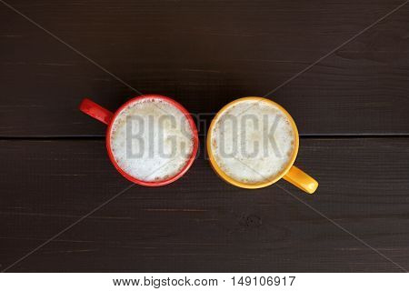 flat layout with a frothy cappuccino in the yellow and red circle top view / autumn mood with a warming drink