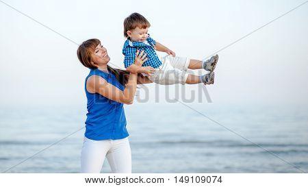 Woman toss the boy up. Behind Ocean and clean sandy beach