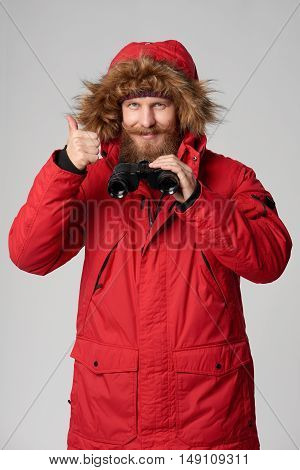 Portrait of a man wearing red winterjacket with hood on, holding binoculars and gesturing thumb up, studio shot