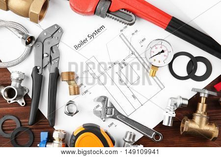 Plumbing tools with house plan on wooden background