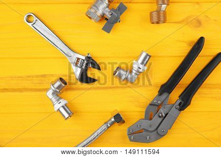 Plumber tools on yellow wooden background