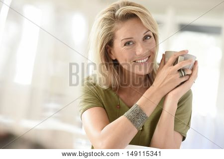 Attractive blond middle-aged woman dinking hot tea