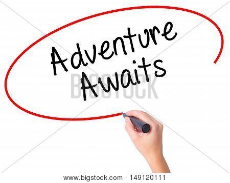 Women Hand Writing Adventure Awaits With Black Marker On Visual Screen