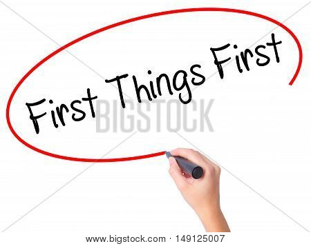 Women Hand Writing First Things First With Black Marker On Visual Screen
