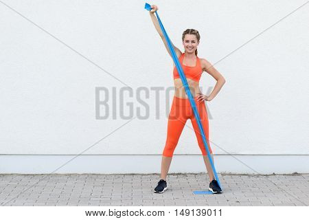 Young Sporty Woman Working Out With Latex Bands