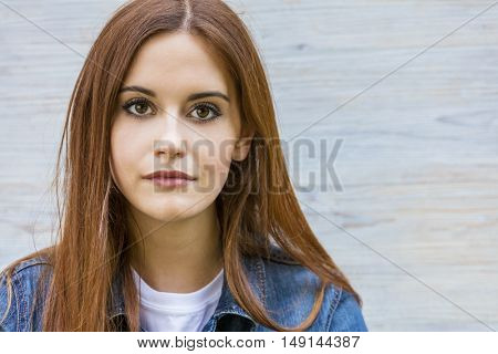 Outdoor portrait of beautiful thoughtful girl or young woman with red hair wearing a blue jeans denim jacket and white t-shirt