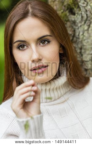 Outdoor portrait of beautiful thoughtful girl or young woman with red hair wearing a jumper and chewing a piece of grass