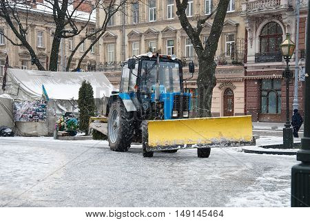 Snow Tractor Clearing Central Square During Snowfall