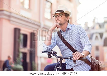 Let me think. Pleasant handsome serious man concentrating on his thoughts and sitting on the bicycle while resting in the city