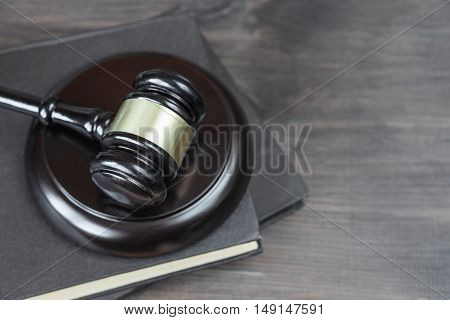 Wood gavel and on the old book on a dark wooden background top view