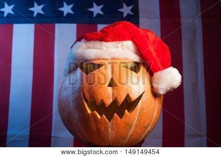 Jack-o '- lantern in a red Santa hat on American flag background, happy holidays, Jack-o ' - lantern-patriot