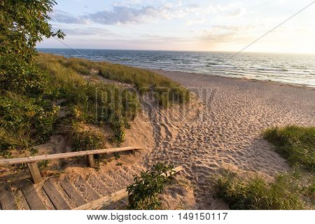 Michigan Summer Beach Vacation. Staircase leads to the wide sandy beach on the coast of  Lake Michigan glowing in the summer sun. Hoffmaster State Park.
