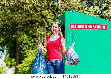 Woman at clothes recycling skip