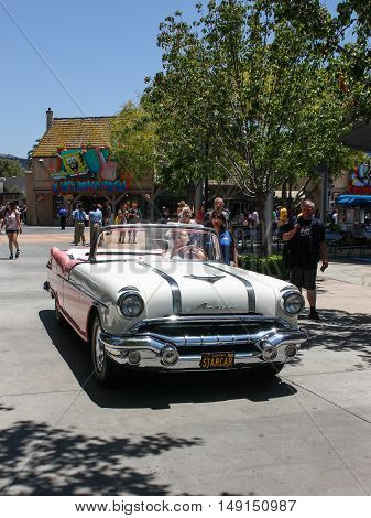 Los Angeles, CA, United States - 15 June 2010. Model in an image of Marilyn Monroe drives through the streets of Universal Studios in Los Angeles Hollywood . Beige Pontiac in retro style perfectly with her dress, hair and glasses.