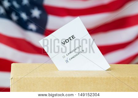 voting and civil rights concept - vote with two candidates inserted into ballot box slot on election over american flag