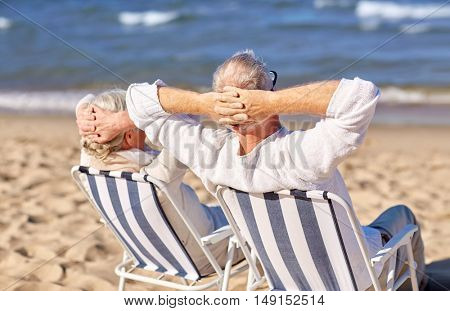 family, age, travel, tourism and people concept - happy senior couple sitting on deck chairs on summer beach