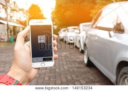 CHIANG MAITHAILAND - SEP 022016 : A womans hand holding Uber application startup page on the Apple iPhone 6 display. Blurred street view with car,  Uber is smartphone app-based transportation network.