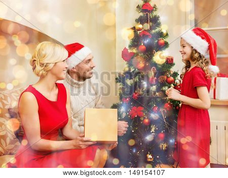family, christmas, x-mas, winter, happiness and people concept - smiling family in santa helper hats decorating christmas tree