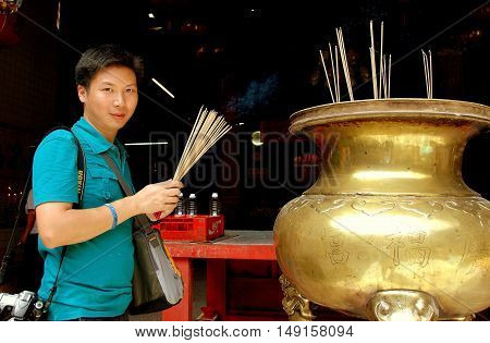 Georgetown Malaysia - January 7 2008: Asian man holding wooden incense sticks standing next to a bronze brazier at the 1801 Guan Yin Chinese temple