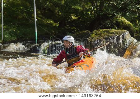BALA WALES UNITED KINGDOM SEPTEMBER 17 2016: White water kayaker at the National White Water Centre canoeing through rapids on the River Tryweryn