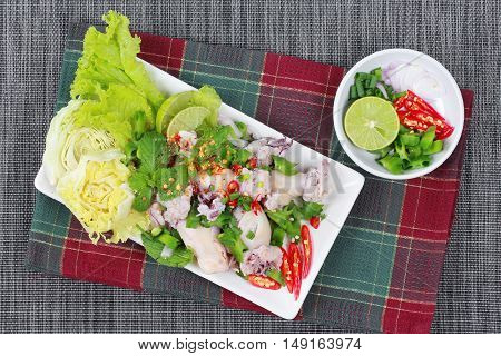 Spicy and sour mixed herb salad with squid wrap minced pork salad  is Thai cuisine as sliced lemon grass,kaffir lime leaves,minced red chili,sliced shallots,parsley and peppermint topped halve green lemon ,red chili and lettuce.