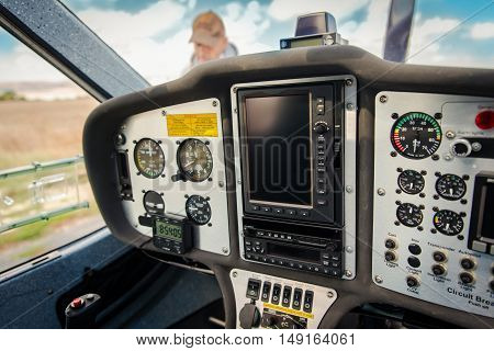 Pilot doing the preflight checks of the aircraft. Selective focus on part of the cockpit and the control panel.