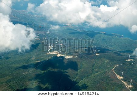 Panorama skyline view of cloudy blue sky from airplane window over wind farm landscape background. Wind turbines renewable power energy stations. Environmentally friendly renewable energy windmill.