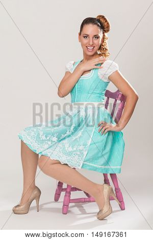 Young Bavarian woman with beautiful hairstyle sitting in Dirndl on a pink wooden chair.