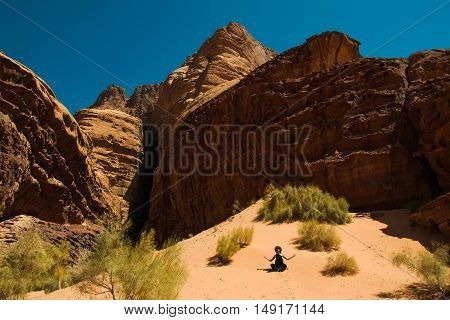 Photo of the Inspiration retreat concept. Girl relaxing meditation in Wadi Rum desert Jordan. Travel lifestyle summer vacations.