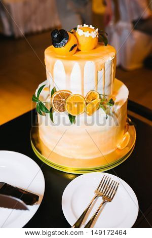 Tiered wedding cake with orange, mandarins and green branch